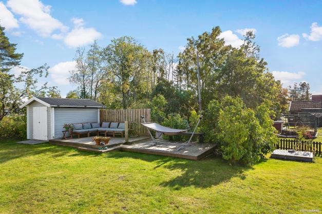 Trädgård med altandäck och förrådsbod, lekstuga och en sandlåda.