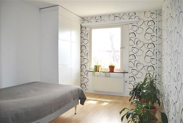 Ljust sovrum med laminatgolv och garderobsmöbel