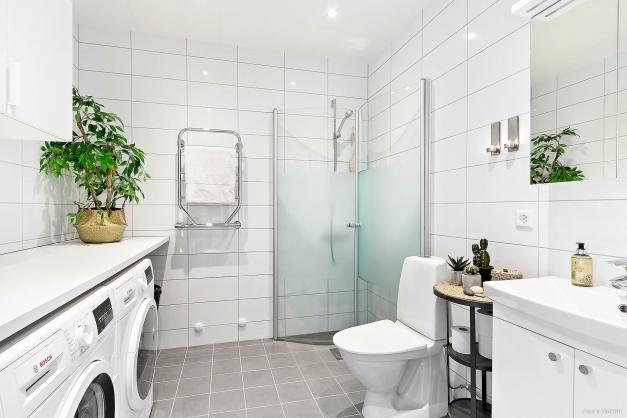 Helkaklat badrum med dusch, tvättmaskin och tumlare.