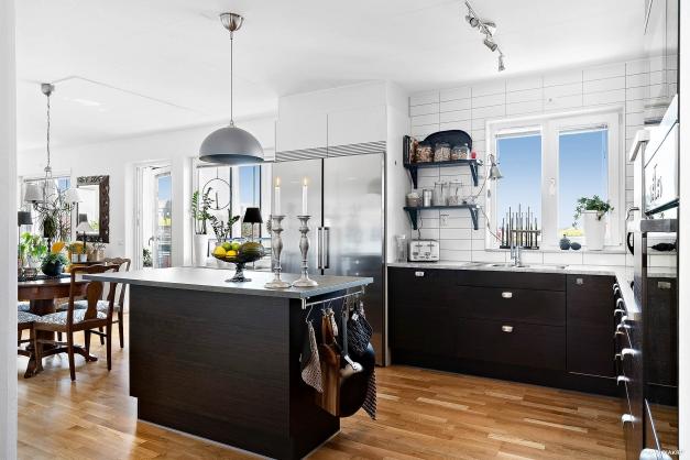 Härligt kök i öppen planlösning med vardagsrum och utgång till inglasad balkong.