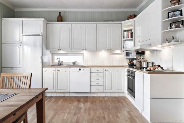 Kök med gott om utrymme för matbord vid fönster.