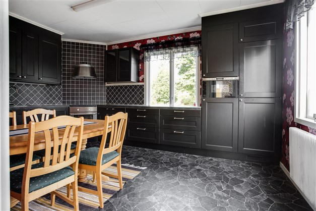 Helrenoverat kök med svart inredning.