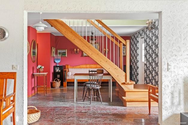 Trappan upp till övervåningen delar av hall och allrum på ett trevligt sätt.