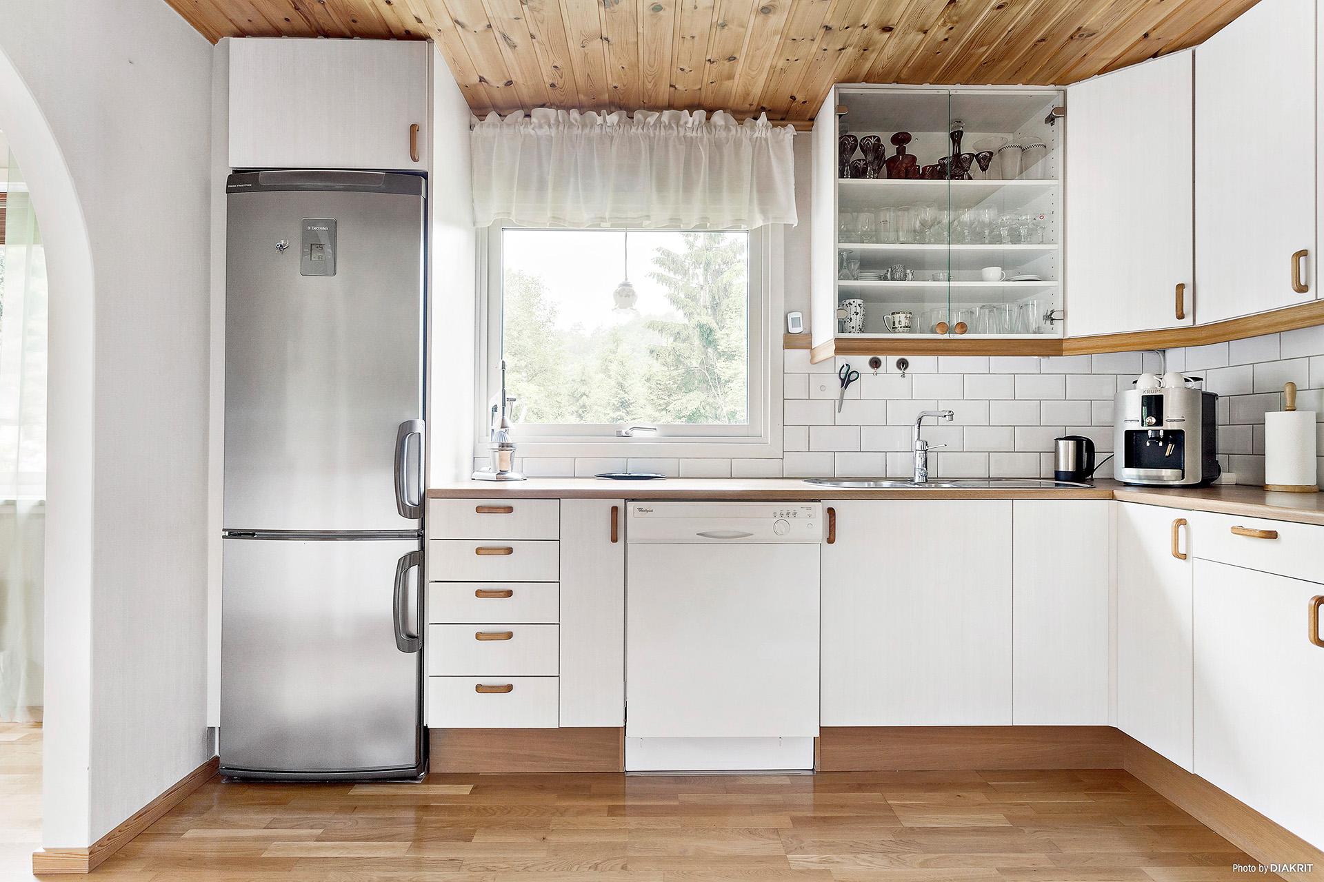 Ljust kök med fönster ovan diskhon