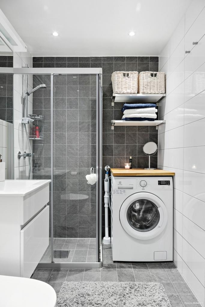 Helkaklat badrum med tvättmaskin och spotlights.
