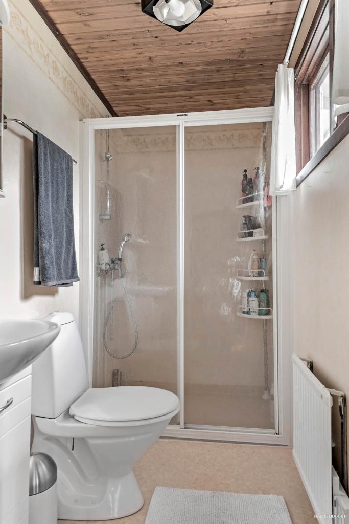 Badrum med dusch, toalett och tvättställ.