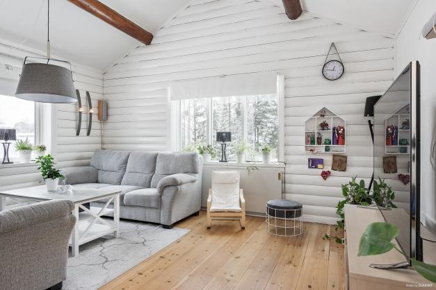 Ljust härligt vardagsrum med ljusinsläpp från två håll och tak öppet till nock med snygga synliga takbjälkar