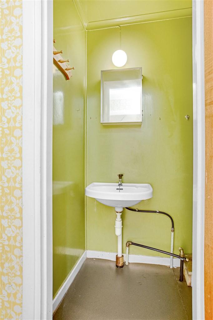 Tvättrum med handfat intill hallen.