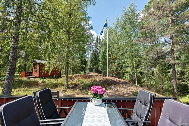 Härligt privat naturtomt med flaggstång. Gäststugan skymtar i bakgrunden.