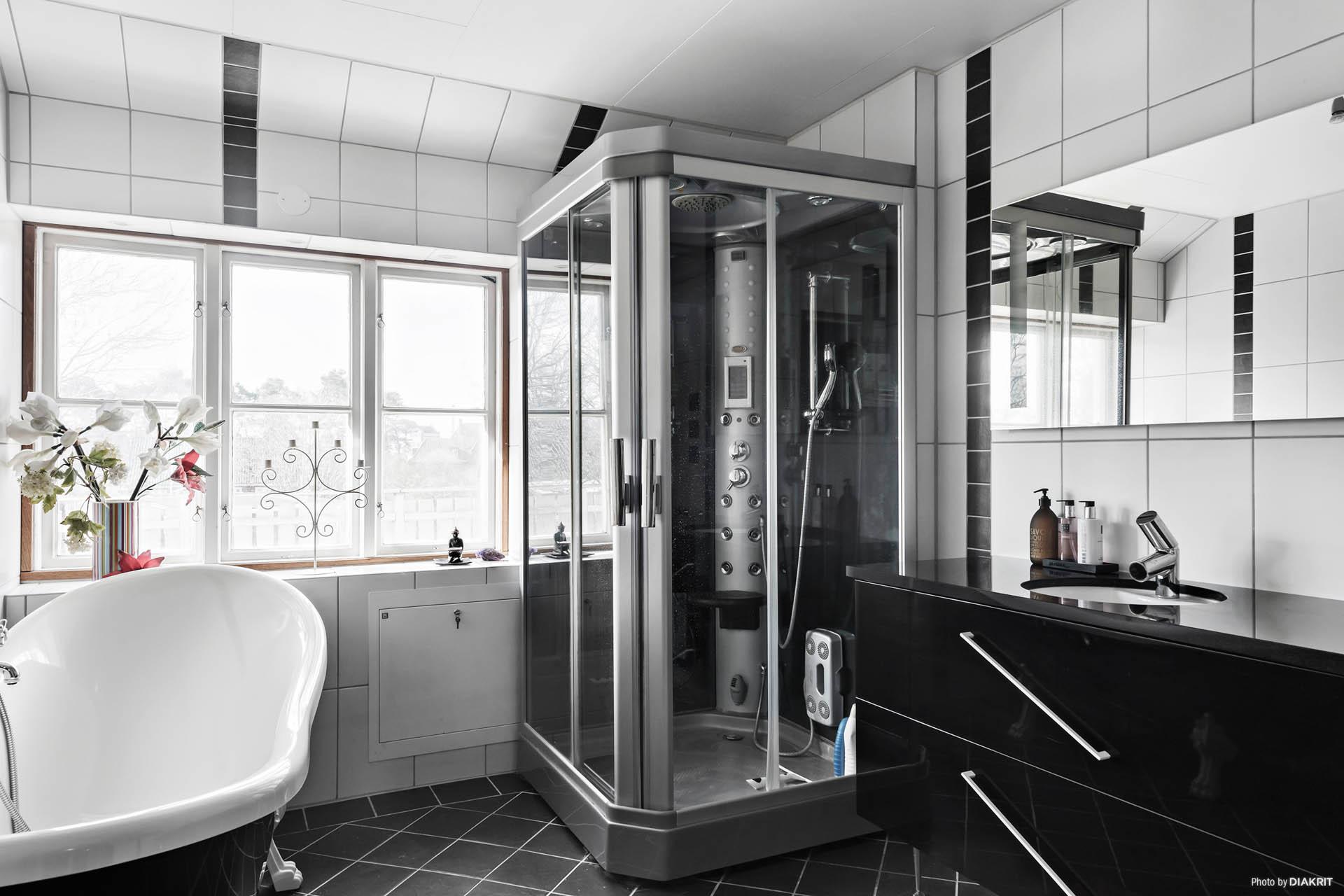 Badrummet är utrustat med badkar, ångdusch, toalett och tvättställ.