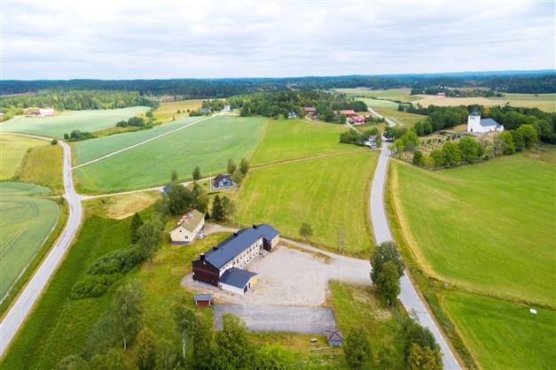 Fastigheten ligger i vacker lantlig miljö. Närmast till vänster ligger den före detta lärarbostaden och i bakgrunden skymtar Rännelanda kyrka