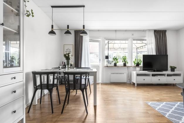 Stort vardagsrum som har plats för både soffa och matgrupp