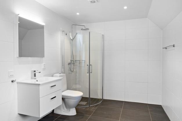 Stort badrum, med tvättmaskin och torktumlare.