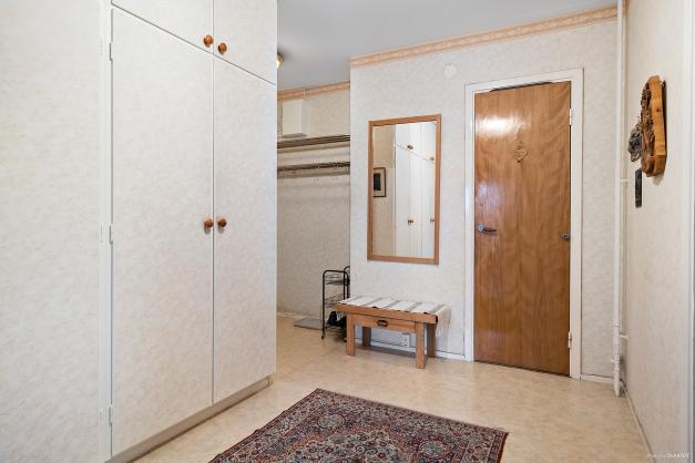 Hallen med vy från vardagsrum mot entré och badrum.