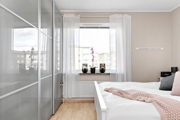 Stort master bedroom med skjutdörrrsgarderob som rymmer längs hela väggen.