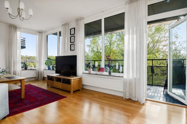 Underbart ljust vardagsrum med utgång till stor balkong
