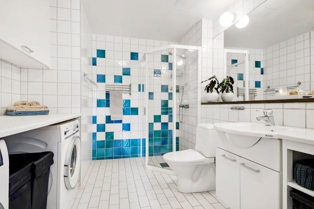 Generöst badrum med tvättmaskin och torktumlare