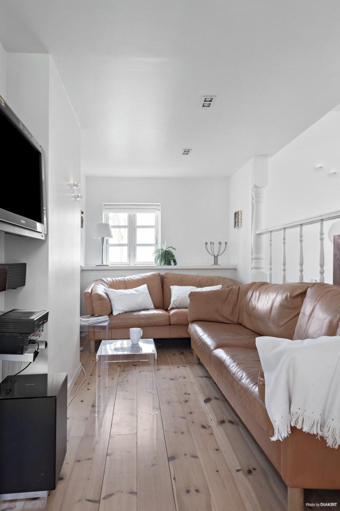 Ett till vardagsrum med plats för tv`n. bakom soffan finns en liten nisch, det är här inkommande vattenkranen sitter, där finns en lucka