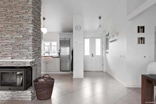 Vi går in i huset. Här råder öppen planlösning och köket och den murade spisen är centrum i huset. Klinkergolv i hela huset med elgolvvärme samt ljust målade ytor i övrigt