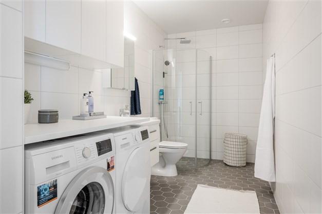 Duschrum med tvättmaskin och tumlare, smakfullt kakel/klinkers samt golvvärme