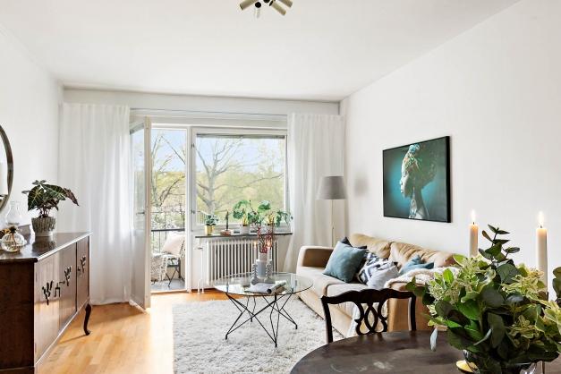 Vardagsrum med plats för både soffa och matbord. Utgång till solig balkong