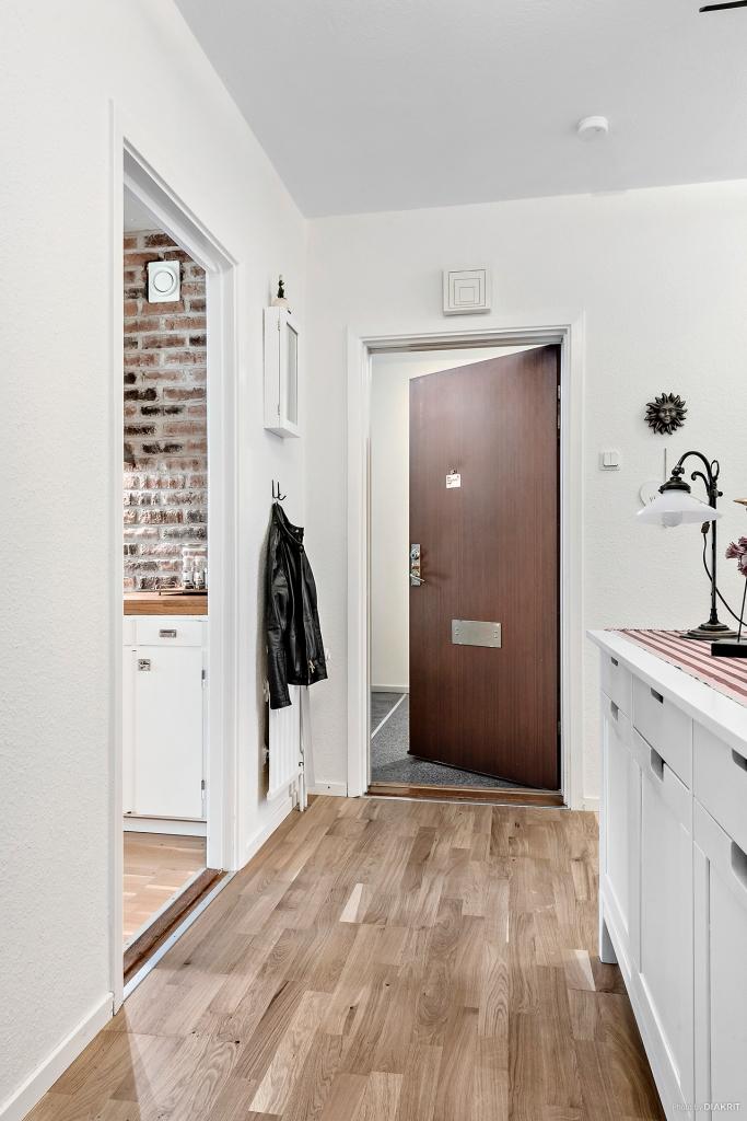 Hall och entré. Hela lägenheten är ljust målad och det ligger ekparkett i alla rummen.
