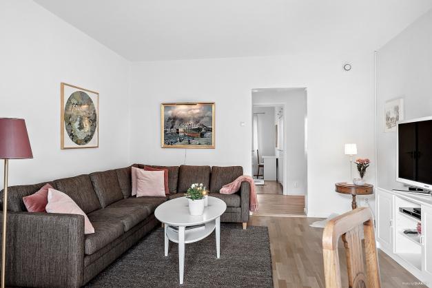 Rymligt och ljust vardagsrum som rymmer stor soffa, medierna och matbordet