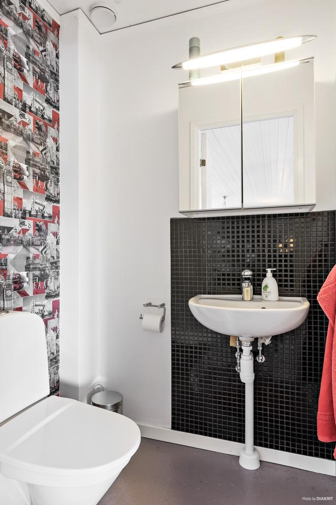 Gästtoaletten är även den snygg och har en klassisk färgsättning i svart och vitt, upphottat med en mönstrad tapet.