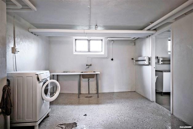 Gemensam tvättstuga med tvättmaskin och tvättho.