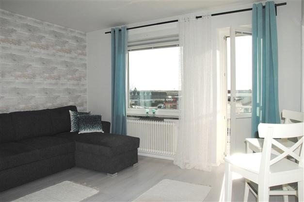 Ljust laminatgolv och ljusa tapeter ger en ljus och trevlig lägenhet