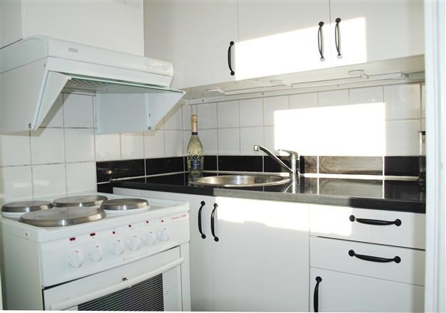 Kökspentry med vita släta köksluckor, belysning över köksbänk m.m.