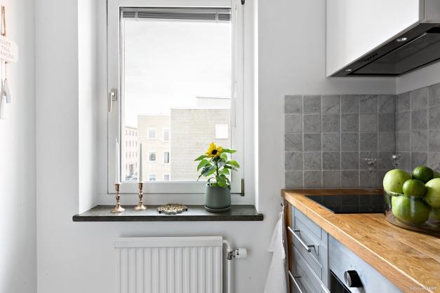 Med en smakfull kombination av material i grått, vitt och trä ger köket, liksom lägenheten i helhet, ett fantastiskt intryck som garanterar både ett modernt och rofyllt boende