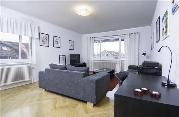 Härligt vardagsrum med fiskbensmönstrat parkettgolv, fönster åt två håll och utgång till balkong