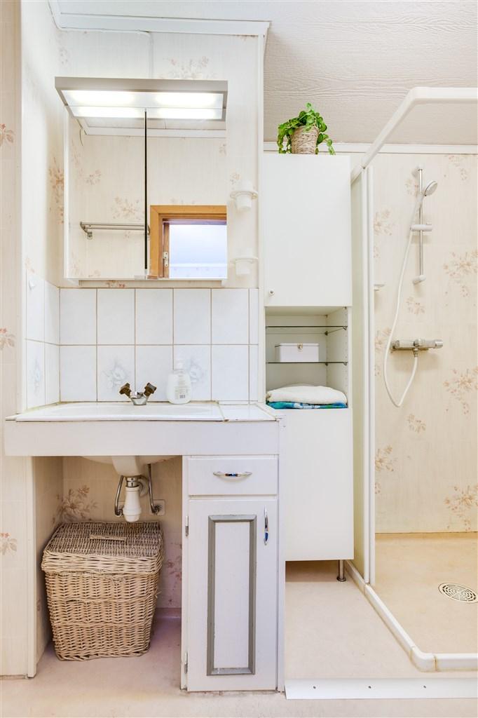 Dusch/wc med inbyggt handfat och linneskåp för förvaring.