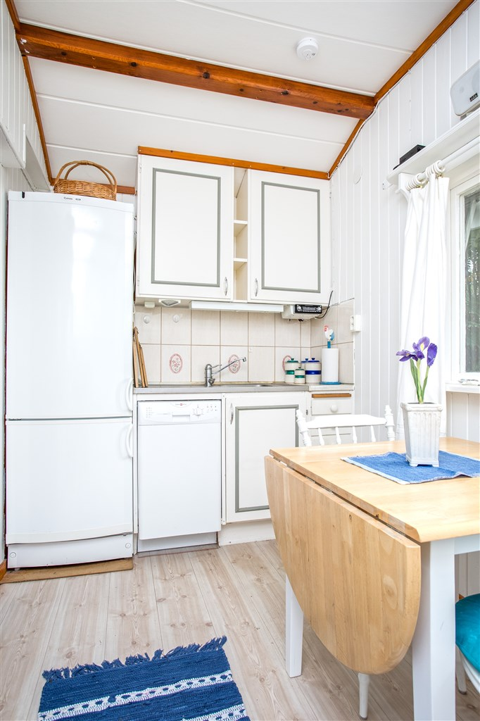 Kök med vita köksluckor och kakel över diskbänk. Diskmaskin.
