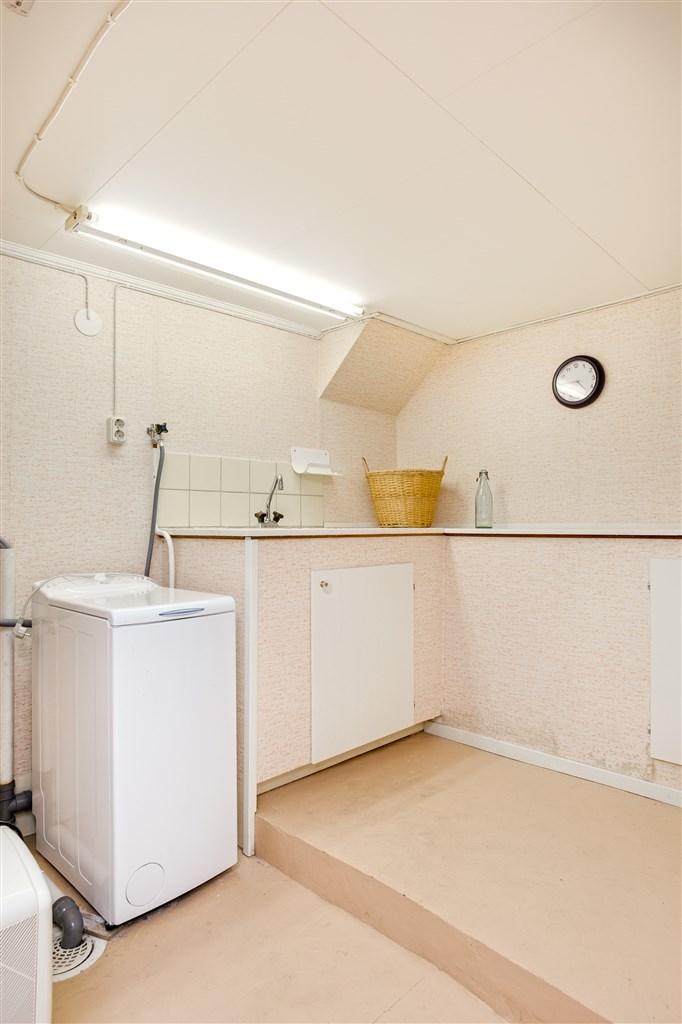 Hobbyrum/tvättstuga med arbetsbänk med diskho. Här finns tvättmaskin.