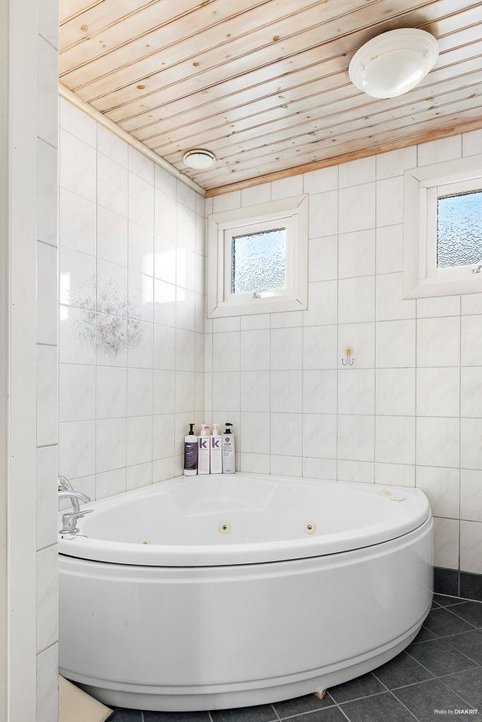Badrum med helkaklade väggar och grått klinkergolv. Gott med förvaring och härligt badkar.
