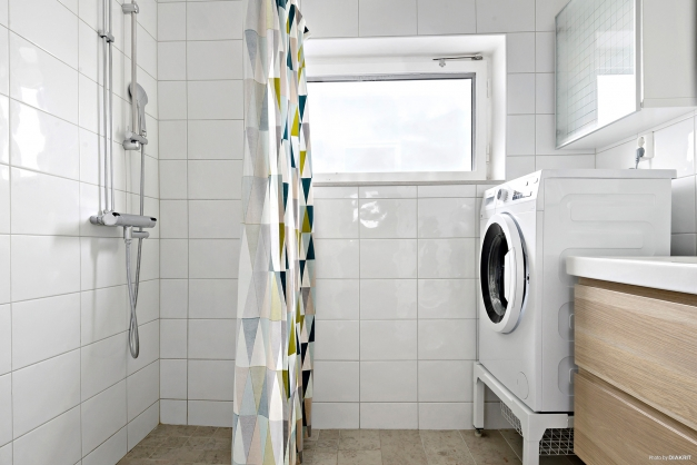 Helkaklat duschrum med förhöjd tvättmaskin