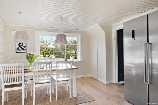 Köket har en avskild matplats framför de stora fönsterpartiet.