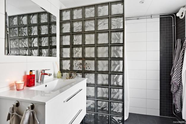 Helkaklat och fräscht badrum inrett med både tvättmaskin och torktumlare.