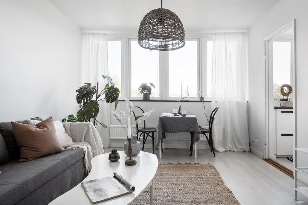 Ljust och smart planerat vardagsrum med matplats invid fönstret.