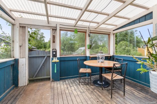 Inglasad altan i anslutning till kök med utgång mot trädgård och baksida