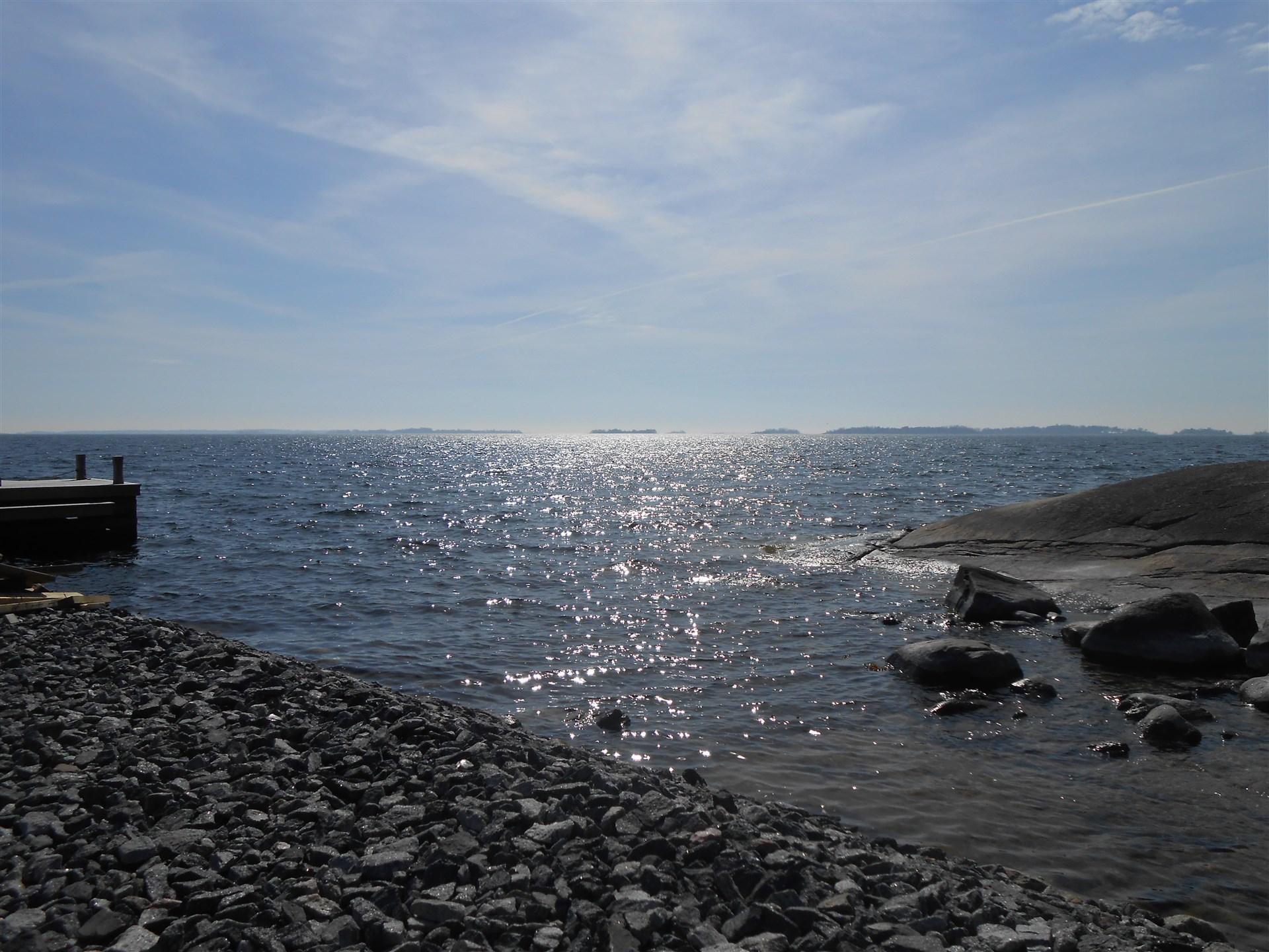 Vy från strand vid båtbryggan sommartid