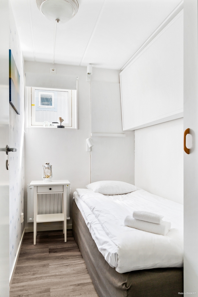 Sovrum med säng samt en extra nedfällbar vägghängd säng
