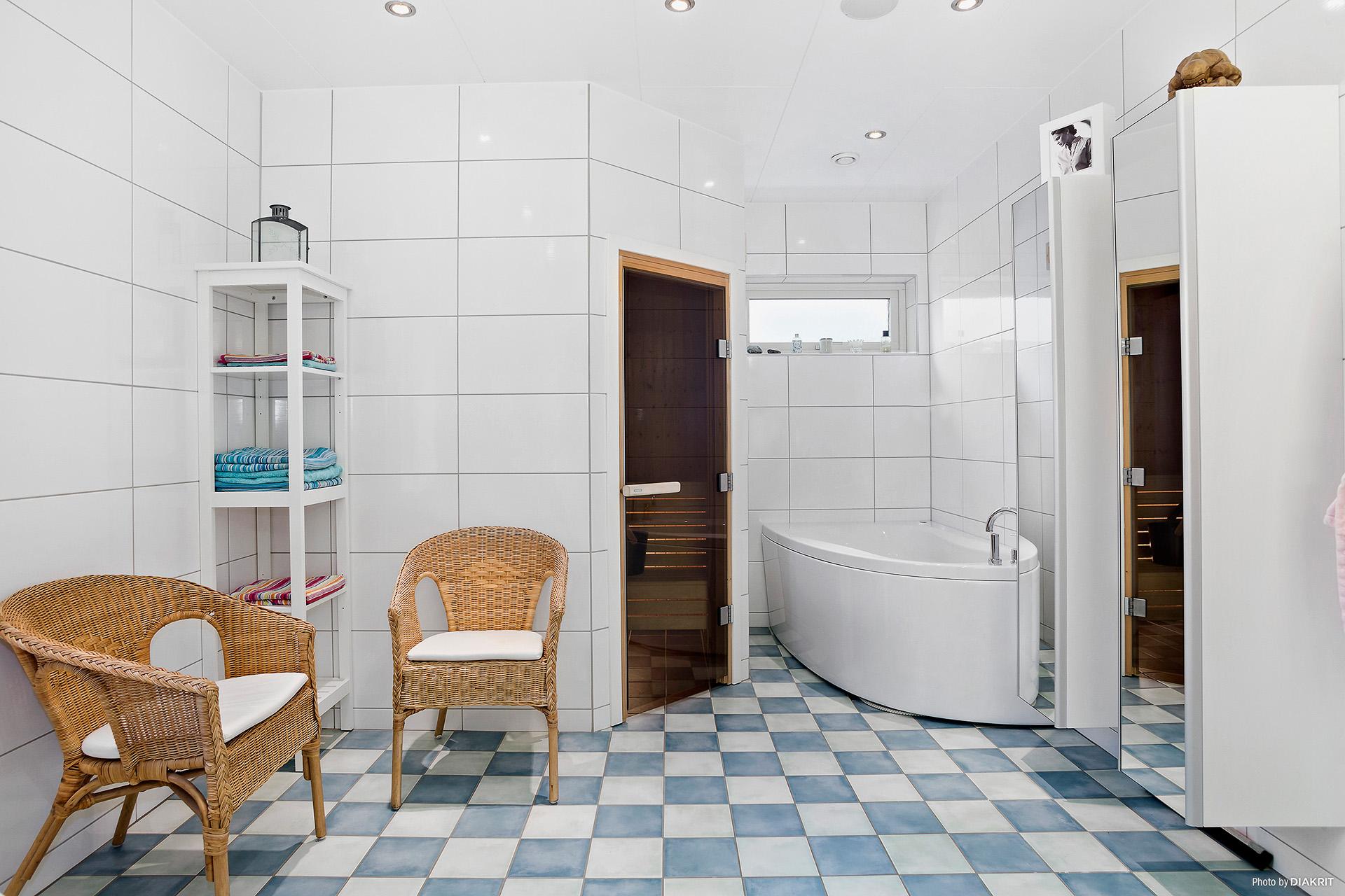 Ett stort, helkaklat badrum med både badkar, dusch och bastu