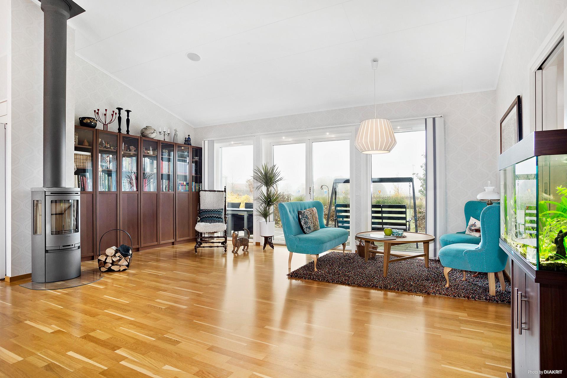Vardagsrum med baskamin och stora fönsterpartier ut mot altanen och trädgården