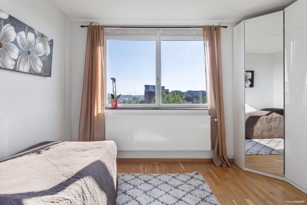 Det andra sovrummet med stort fönsterparti mot innergården