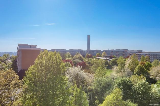 Utsikt från balkongen. Grönska, fotbollsplan, lekplatser m.m.