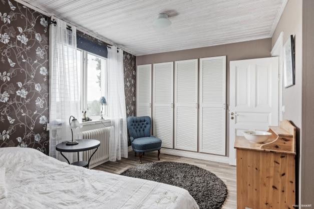 Sovrum med 4 garderobsdörrar som leder till en klädkammare
