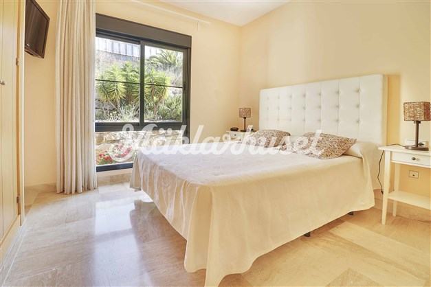 Master bedroom med utsikt till grön innegård.